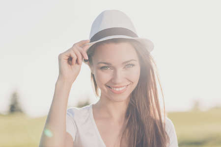 Young gorgeous brunette girl on a spring vacation, in a stylish hat, casual outfit, holding her cap, so dreamy and charming, smiling