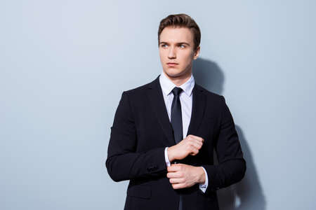 Young handsome businessman banker in a suit is fixing his cuff links, he stands on pure light background. So mature and virile, hot and confident