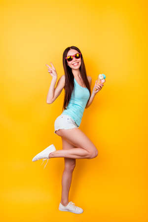 Full length of funky young korean lady is posing for vacation photo shot, wearing tourist`s outfit, glasses, holds ice cream. Happiness, dream, fun, joy, freedom concept
