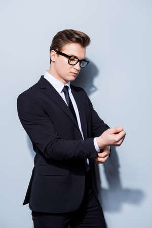 Young handsome businessman lawyer in a suit is fixing his cuffl inks, he stands on pure light background. So mature and virile, hot and confident