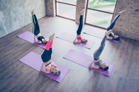 Upside down seal pose. Topview of five pretty young slim ladies, stretching by doing shoulderstand exercise, wearing fashionable sport wear, barefoot on a purple carpet Stock Photo