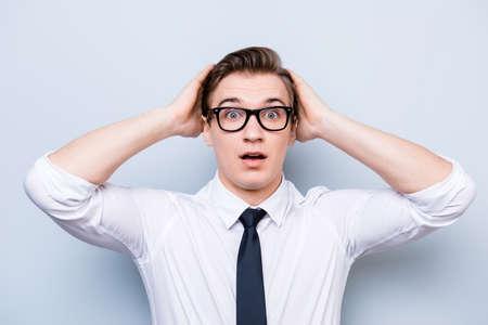 Uau! Mesmo?! Jovem estudante bonito está chocado, segurando a cabeça dele, em uma roupa formal e óculos elegantes preto, em pé no fundo puro Foto de archivo - 86357225