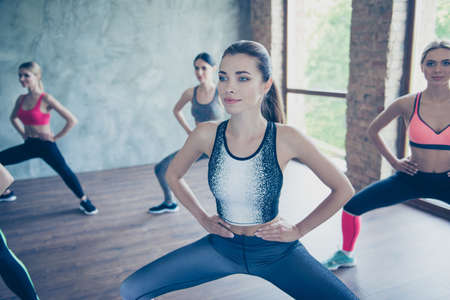 Close up of a pretty sporty lady, training. Five young slim ladies are stretching their legs and arms by doing squat exercise, wearing fashionable sport wear, smiling