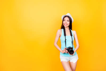 Cute asian teen photographer on summer vacation. She is holding camera, wearing summer casual outfit and a hat, poses on bright yellow background