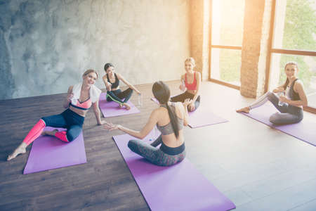 Five cheerful girls are resting after work out, drinking water, talking, laughing, sitting on purple mats, smiling in modern studio