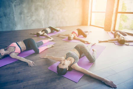 Spinal twist. Five young sport women are stretching in modern studio on purple mats. Freedom, calmness, harmony and relax, women happiness concept