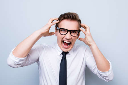 Going crazy and insane. Close up portrait of shouting stressed young entrepreneur in a formal wear and glasses, standing on pure light background Stock Photo