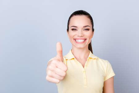 Ich mag das! Junges nettes Mädchen, stehend auf dem reinen hellblauen Hintergrund und lächelt, ein gelbes T-Shirt tragend und thumbup Zeichen