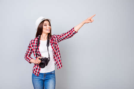Happy young brunette lady tourist is on vacation, in casual outfit, hat and with camera, isolated on pure background Stock Photo