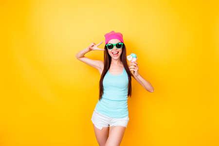 アジアのファンキーなヒップスターは、写真のためのポーズ、観光客の服を着て、メガネ、帽子、アイスクリームを保持しているので、スリムで魅