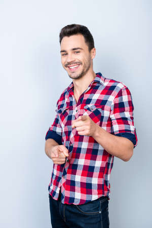 Smiling young stylish bearded brunet student in bright casual checkered shirt is standing on light background and point on camera with flirty smile and glance