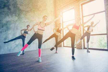 Body care time. Five pretty young slim ladies are stretching their legs and arms by doing exercise, wearing fashionable sport wear, sneakers, smiling