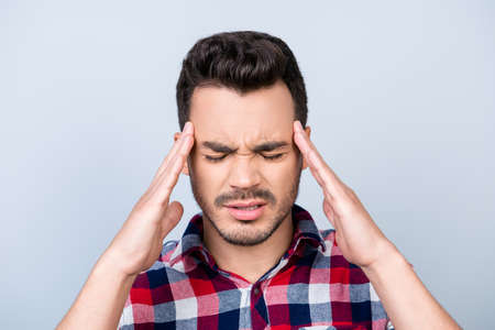 Head is blasting, strong migraine. Struggling handsome young man with strong pain grimace. He is wearing the casual ckeckered shirt, standing on pure background