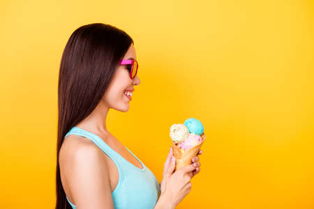Side profile photo of excited young asian lady, holding tasty ice cream of three scoops of different flavors, stands on yellow background in tourist wear, glasses