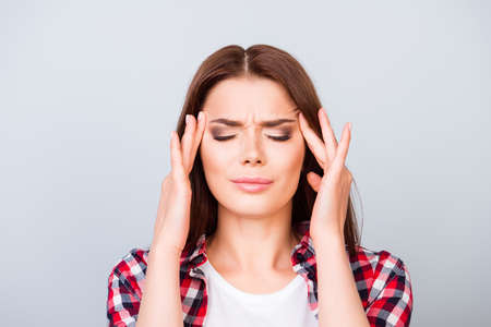 Head is blasting, strong migraine. Struggling beautiful young lady with strong pain grimace. She is wearing the casual outfit, standing on pure background