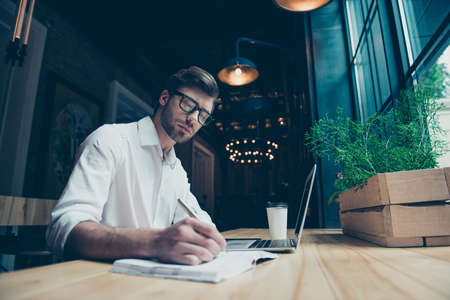 Young stylish well dressed author writer is working in a modern coworking, writing the novel, in glasses, so serious and focused
