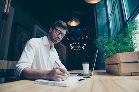 Un escritor joven, elegante y bien vestido, está trabajando en un moderno coworking, escribiendo la novela, en lentes, tan serio y concentrado.