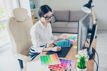 Drukke jonge Aziatische grafisch ontwerper trekt iets op grafische tablet op kantoor, gericht. Ze is een succesvolle zelfstandige kunstenaar
