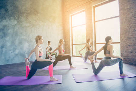 Five young slim yoga ladies are making stretching exercise on the purple mats, so fit and healthy, wearing modern sport outfit, barefoot in modern studio Stock Photo