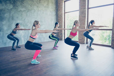 Work out and wellbeing time. Five pretty young slim ladies are stretching their legs and arms by doing squat exercise, wearing fashionable sport wear, sneakers, focused