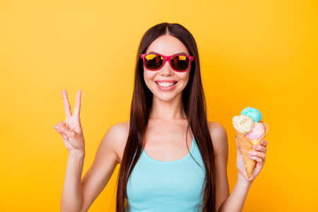 Funky young asian lady is posing for vacation photo shot, wearing tourist`s outfit, glasses, holds ice cream, has a beaming toothy smile