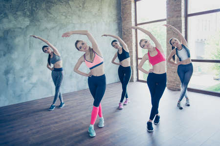 Five young fashionable sportswomen are stretching, so bendy and flexible, wearing trendy sport outfit, shoes, training in the modern studio Stock Photo