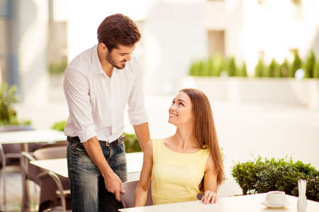 True gentleman! Young handsome brunet lover is adjusting the chair of his happy lady, both well dressed, at a sunny terrace of restaurant Stock Photo
