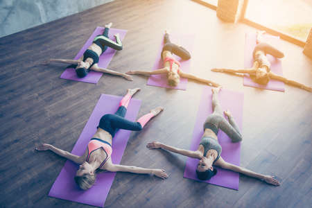 Topview of spinal twist, five young sporty women are doing in modern studio, lying on purple mats. Freedom, calmness, harmony and relax, women happiness concept
