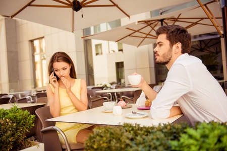Relationship problems. Lady is talking very quiet on her smart phone, covering her mouth with the palm of hand, whille sitting on a date with guy