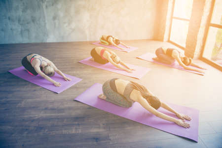 Calm and peace concept. Five young slim yoga ladies are making stretching lying on the purple mats, so relaxed Stock Photo