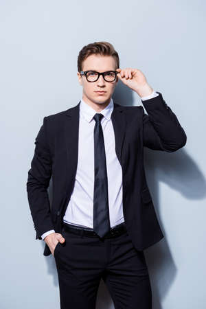 Successful young handsome businessman banker in a suit is fixing his glasses, he stands on pure light background. So mature and virile, hot and confident