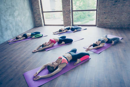Five young slim yoga ladies are making stretching lying on the purple mats, so relaxed and healthy, wearing modern sport outfit, barefoot in modern studio