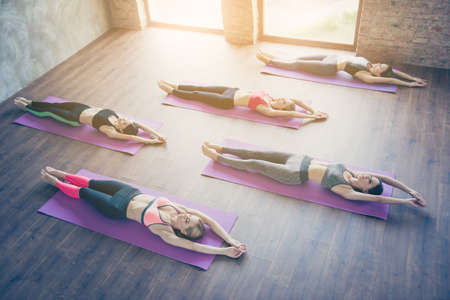 Topview of five young slim yoga ladies, stretching their whole bodies, lying on the purple mats, so relaxed and healthy, wearing modern sport outfit, barefoot in modern studio