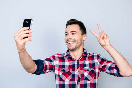 Selfie time! Young funky blogger is making photo for his social networks page, he is posing in a casual outfit and gesturing peace sign