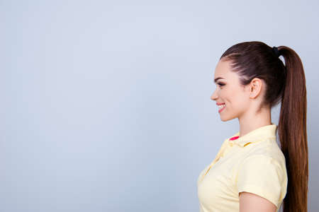 Profile portrait of young lady in yellow tshirt with ponytail, toothy smile on pure background with copy space