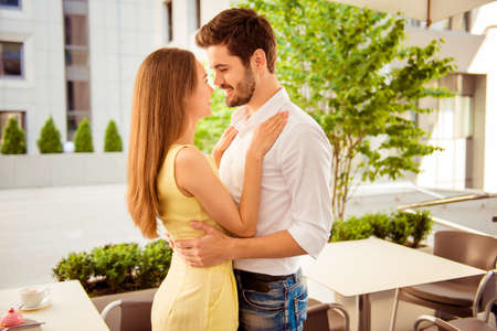 A moment before kiss. Happy young couple in love is hugging and looking deep into eyes of each other, well dressed, at the summer terrace of a cafe Stock Photo