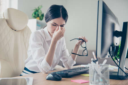 Exhausted young asian entrepreneur lawyer is holding his nose bridge with closed eyes, she is tired and depressed. She is sitting at her work place, holding eyewear Banco de Imagens