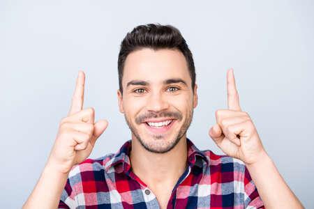 見て!笑顔を発する若い陽気な男は、彼の指で、カジュアルなシャツを着て、光の背景に立っている