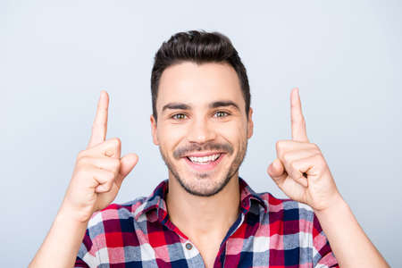 Look up! Young cheerful man with beaming smile is pointing up with his fingers, wearing casual shirt, standing on light background isolated Фото со стока