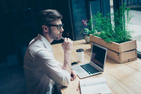 フォーマルな摩耗で若い男は夢を熟考することは、ロフトスタイルの現代のコワーキングスペースで彼の仕事の場所に座っていると、窓を見て、考