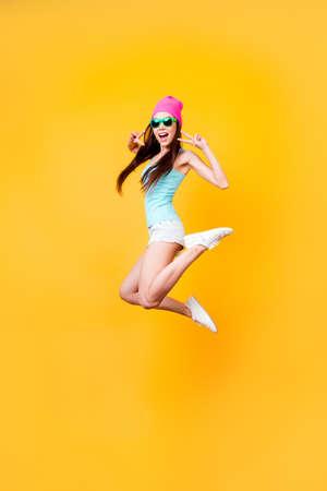 Wow! Felicità, sogno, divertimento, concetto di gioia. Adolescente asiatico sveglio felice molto eccitato sta saltando su, indossando abiti estivi casual, scarpe bianche, su sfondo giallo brillante