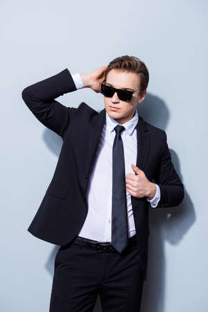 Confident handsome young business man is standing on the pure background in sun glasses and suit, fixing his perfect hairstyle. So hot and attractive, harsh and fashionable Stock Photo