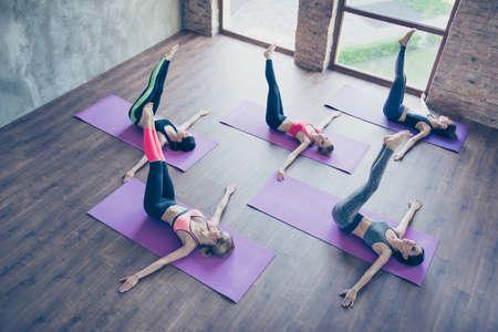 Links rechts! Topview der spinalen Torsion, tun fünf junge sportliche Frauen im modernen Studio und liegen auf purpurroten Matten. Hände auf dem Bretterboden, Beine hoch