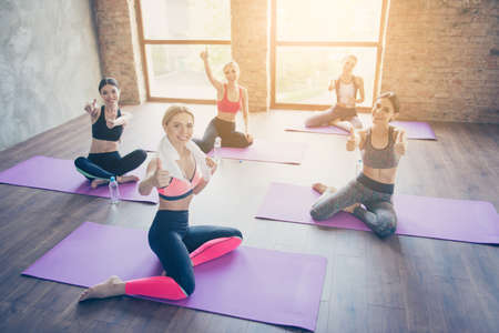You can do it! Five hot ladies in trendy sports outfit are showing thumbups in a gym, sitting on a purple mats, so slim and attractive Фото со стока
