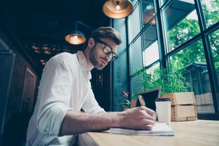 若いスタイリッシュな格好の著者の作家の Yow アングルビューは、現代のコワーキングスペースで働いている、小説を書いて、眼鏡で、非常に深刻な