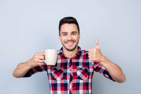 Great job! Very excited young  brunet bearded freelancer is gesturing like sign, he finished the project, now it`s coffee time, chill and relax Stok Fotoğraf - 86357318