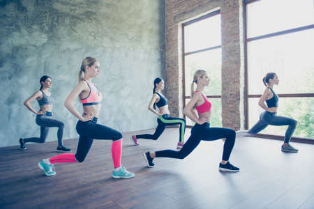 Five young fashionable sportswomen are stretching their legs by doing squats, so bendy and flexible, wearing trendy sport outfit, shoes, training in the modern studio Stock Photo