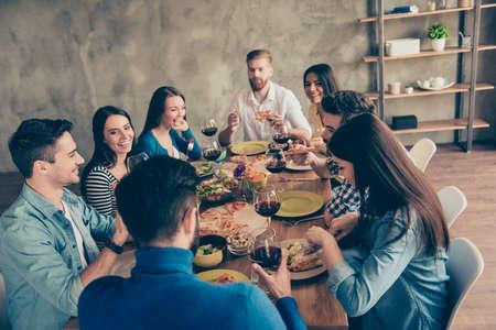 Geweldig weekend samen. Groep van jonge vrolijke mensen plezier thuis op het feest met lekker eten, drinken, grappen, genieten en lachen Stockfoto