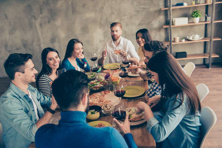 Great weekend together. Group of young cheerful people are having fun at home on the party with tasty food, drinks, jokes, enjoying and laughing Stock Photo