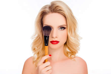 Beauty and cosmetology concept. Close up portrait of pretty blond with bright makeup hiding eye behind make-up brush isolated on white background
